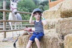 Всадник мальчика приспосабливает его шлем стоковые изображения rf