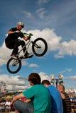 Всадник BMX выполняет эффектное выступление над 3 членами аудитории на ярмарке стоковая фотография rf