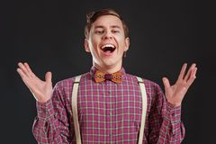 Всегда победитель! Красивый молодой ученый в винтажной рубашке и бабочке показывать держащ руки поднимающим вверх и смеющся над п Стоковые Фото