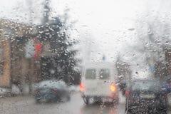 Всегда управляйте автомобилем с осторожностью когда оно идет дождь Идите дождь на улице города через лобовое стекло автомобиля Стоковое Изображение
