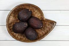 4 всех зрелых коричневых авокадоа в деревянном высекаенном шаре на белом bo стоковое фото rf
