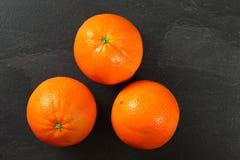 3 всех оранжевых цитрусового фрукта на черной доске шифера, плоском по стоковое фото rf
