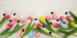 2 всех пасхального яйца принципиальной схемы цыпленока ведра цветут детеныши покрашенные травой помещенные Розовые тюльпаны и пас Стоковая Фотография RF