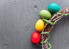2 всех пасхального яйца принципиальной схемы цыпленока ведра цветут детеныши покрашенные травой помещенные яичка и венок на дерев Стоковое Фото