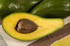 Все авокадоы и авокадо отрезали в половине Стоковое Изображение