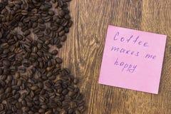Все ароматичные кофейные зерна на деревянном крупном плане предпосылки с примечанием Стоковые Изображения RF