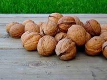 Все грецкие орехи на деревенской старой деревянной близко траве Стоковое Изображение RF