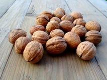 Все грецкие орехи на деревенском старом деревянном столе Стоковые Изображения