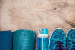 Все для бирюзы спорт, голубых теней на деревянной предпосылке Циновка йоги, ботинки sportswear спорта и бутылка  стоковая фотография