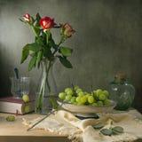 Все еще жизнь с красными розами и виноградинами стоковые фото