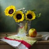 Все еще жизнь с солнцецветами и яблоком стоковое изображение