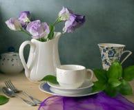 Все еще жизнь с цветками и тарелками стоковое изображение rf