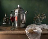 Все еще жизнь с чайником и стеклом красного вина стоковые изображения rf