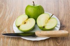 Все зеленое яблоко, половины яблока и нож в плите Стоковое Изображение RF