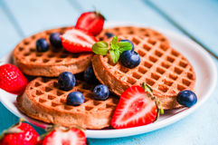 Все зерно waffles с ягодами на голубой деревянной предпосылке стоковые изображения