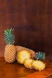 2 все и некоторое вырезывание отрезают ананасы на деревянном столе Стоковые Изображения