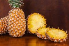 2 все и некоторое вырезывание отрезают ананасы на деревянном столе Стоковые Фотографии RF