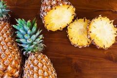 2 все и некоторое вырезывание отрезают ананасы на деревянном столе Стоковая Фотография RF