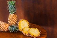 2 все и некоторое вырезывание отрезают ананасы на деревянном столе Стоковое Фото