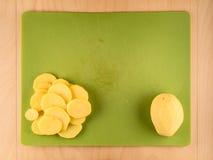 Все и отрезанное potatoe на зеленой пластичной доске Стоковое Изображение RF