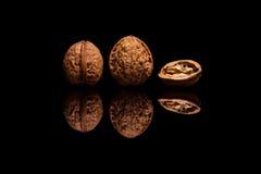2 все и одно уменьшать грецкие орехи на черной предпосылке Стоковые Фотографии RF