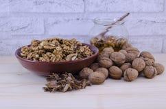 Все и сломленные грецкие орехи и опарник меда Стоковая Фотография