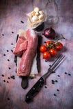 Все мясо tenderloin свинины на винтажной доске с чесноком и томатами Стоковые Фото