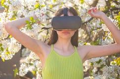 Все настолько реально Милая девушка в шлемофоне виртуальной реальности Милый сад игры девушки весной Молодая дама носит vr стоковое фото