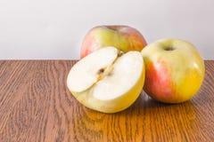 2 все яблоко и половинный лежать на деревянном столе Стоковая Фотография