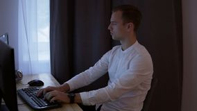Вскользь бизнесмен или frelancer работая дома, сидящ на столе, печатающ на клавиатуре, смотря экран компьютера серо акции видеоматериалы