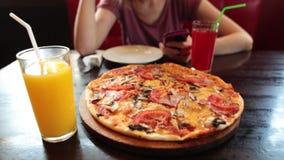 Вскользь девушка используя smartphone в кафе Свежие сок и пицца на переднем плане сток-видео