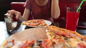 Вскользь девушка перчит часть пиццы, ест ее при вилка и нож, сидя в ресторане сток-видео