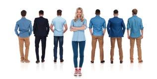 Вскользь женский руководитель стоит за ее командой людей стоковое изображение rf