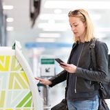 Вскользь кавказская женщина используя умную машину применения и регистрации телефона на авиапорте получая посадочный талон стоковое изображение rf