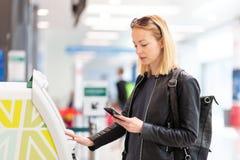 Вскользь кавказская женщина используя умную машину применения и регистрации телефона на авиапорте получая посадочный талон стоковое фото rf