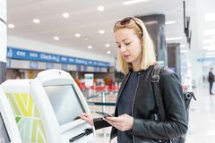 Вскользь кавказская женщина используя умную машину применения и регистрации телефона на авиапорте получая посадочный талон Стоковая Фотография