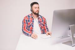 Вскользь молодой человек с шлемофоном используя компьютер в ярком офисе стоковые фотографии rf