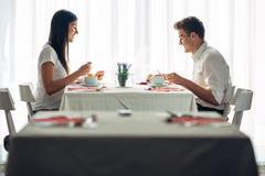 2 вскользь молодых взрослого имея переговор над едой Официальное предложение, говоря в ресторане Пробуя еда, предложения, специал стоковые изображения