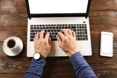 Вскользь одетые студент/блоггер/писатель/человек работая на компьтер-книжке ПК, печатающ на клавиатуре, пишущ статью блога, выпив стоковые фото