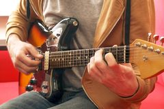 Вскользь одетый молодой человек при гитара играя песни в комнате дома Онлайн концепция уроков гитары Мужской практиковать гитарис Стоковые Фото