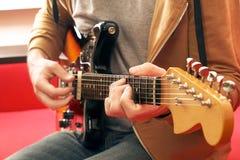 Вскользь одетый молодой человек при гитара играя песни в комнате дома Онлайн концепция уроков гитары Мужской практиковать гитарис Стоковое фото RF
