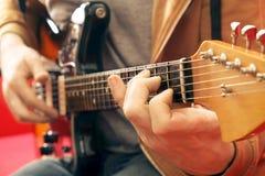 Вскользь одетый молодой человек при гитара играя песни в комнате дома Онлайн концепция уроков гитары Мужской практиковать гитарис Стоковые Изображения