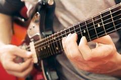 Вскользь одетый молодой человек при гитара играя песни в комнате дома Онлайн концепция уроков гитары Мужской практиковать гитарис Стоковые Изображения RF