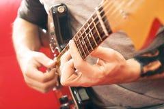 Вскользь одетый молодой человек при гитара играя песни в комнате дома Онлайн концепция уроков гитары Мужской практиковать гитарис Стоковое Фото