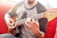 Вскользь одетый молодой человек при гитара играя песни в комнате дома Онлайн концепция уроков гитары Мужской практиковать гитарис Стоковая Фотография RF