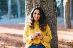 Вскользь послание женщины на умном телефоне в осени стоковое фото