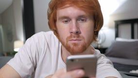 Вскользь сидя человек Redhead используя Smartphone, просматривая акции видеоматериалы