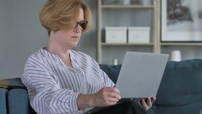 Вскользь старая старшая женщина приходя для работы на компьтер-книжке сток-видео