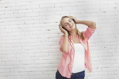 Вскользь белокурая девушка наслаждается слушая наушниками музыки нося стоковые изображения rf