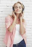 Вскользь белокурая девушка наслаждается слушая наушниками музыки нося стоковое изображение rf
